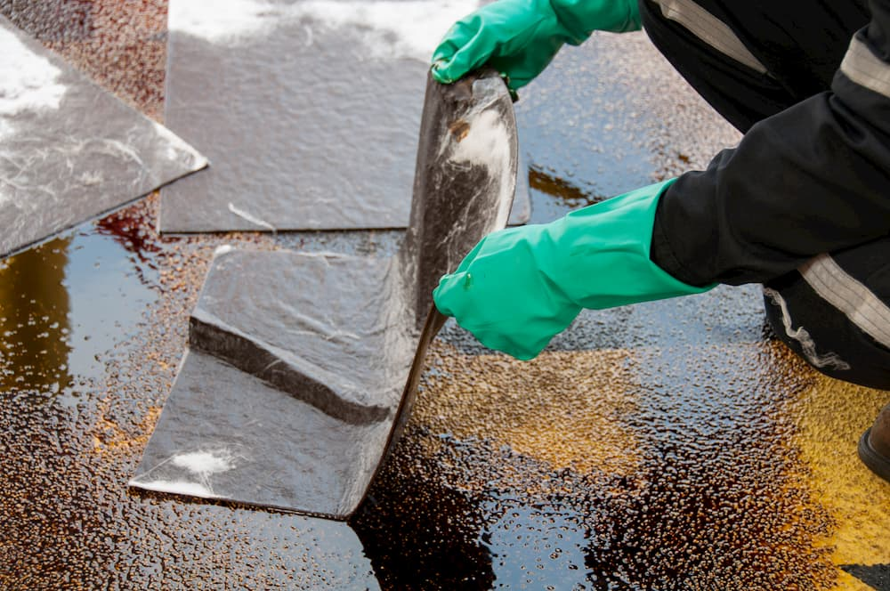 Cleaning up oil spill wearing protective gear