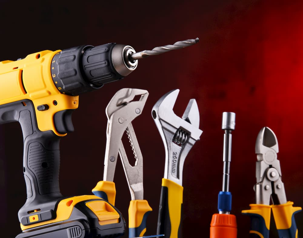 Composition with different kinds of hardware tools including cordless drill, monkey spanner and screwdriver