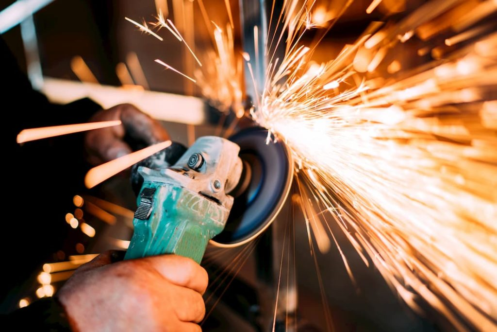 man using electric handheld grinder creating sparks