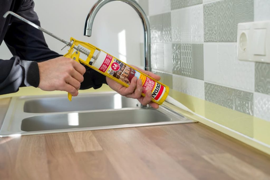 builder applying adhesive in seam between wall tiles and kitchen counter