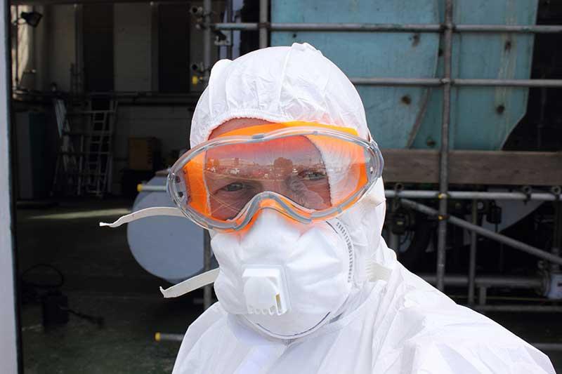 man in white biohazard overalls