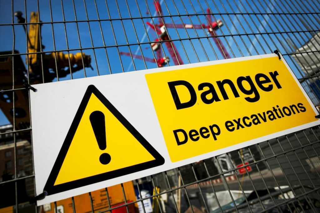 danger safety sign fastened to a metal work site fence