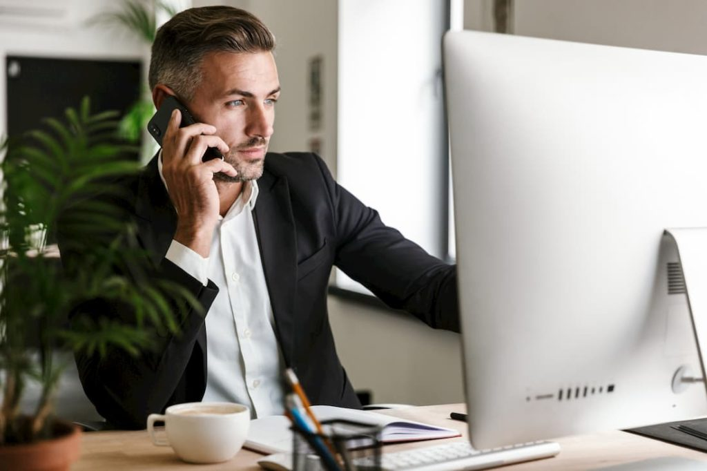 business specialist in product sourcing using mobile phone looking at computer screen