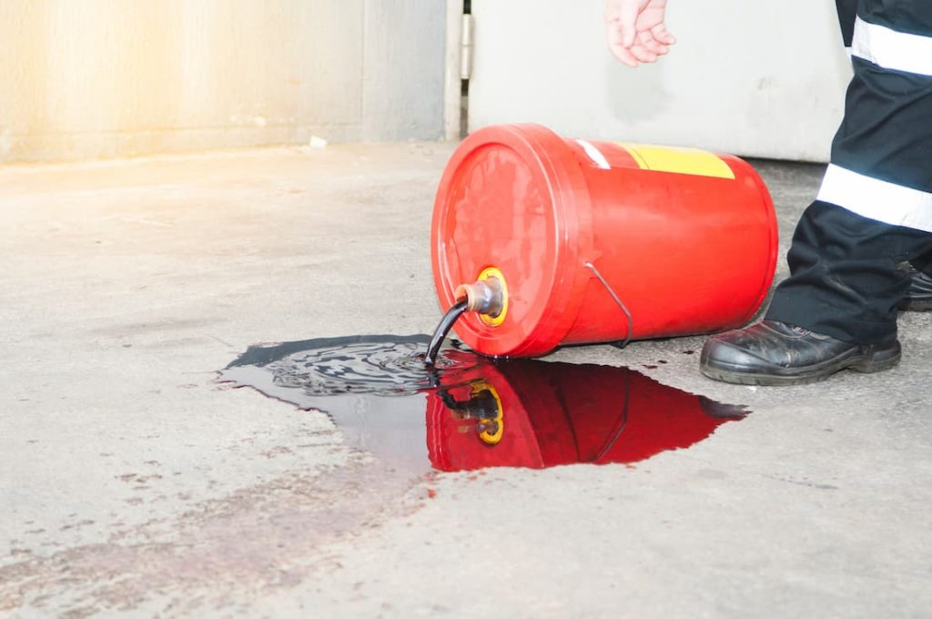 red oil bucket knocked on side spilling oil on floor
