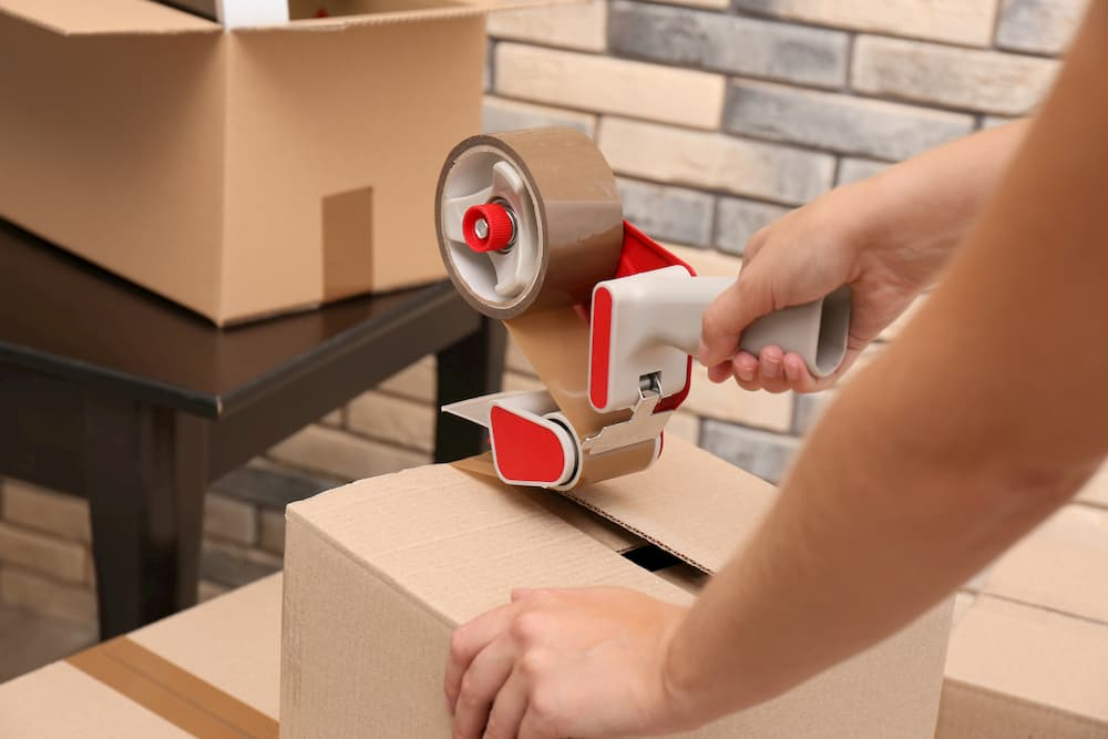 Woman packing carton box indoors, closeup. Moving day