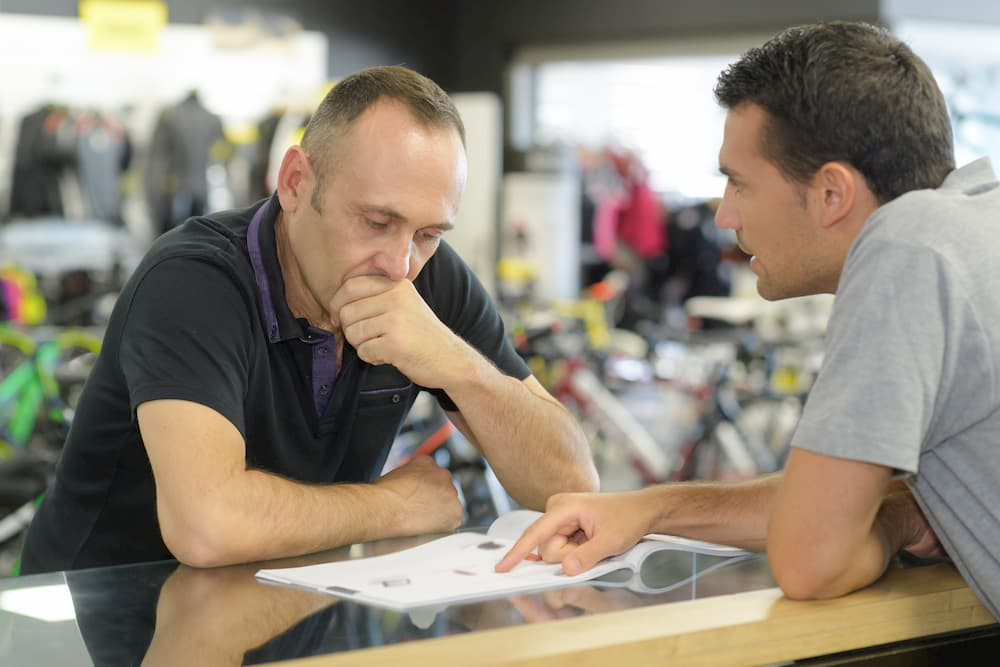 man deciding on products at trade counter with advisor